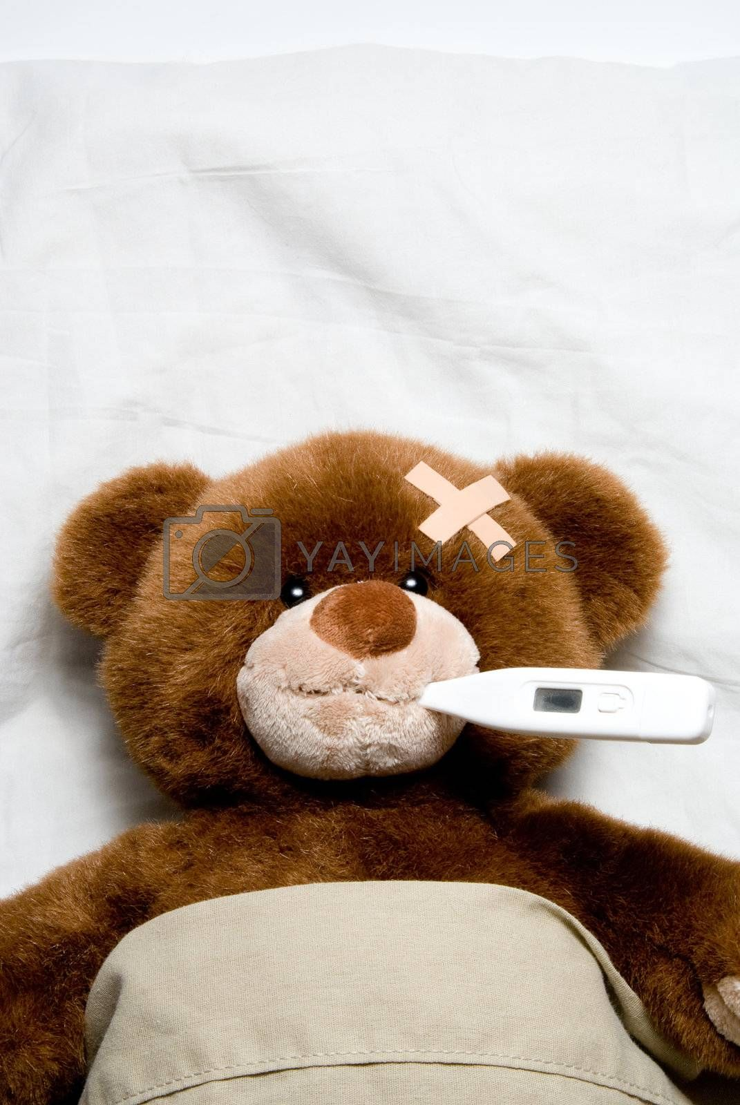 A very Sick Teddy Bear laying in a bed.
