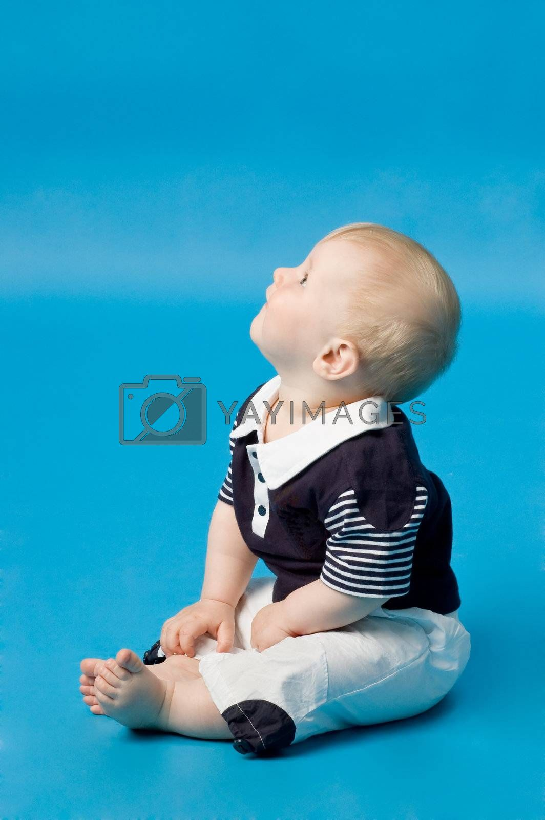 The small child in studio, on a blue background