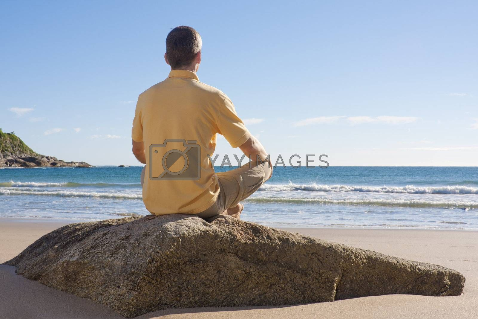 Royalty free image of Man meditating on a beach by ArtmannWitte