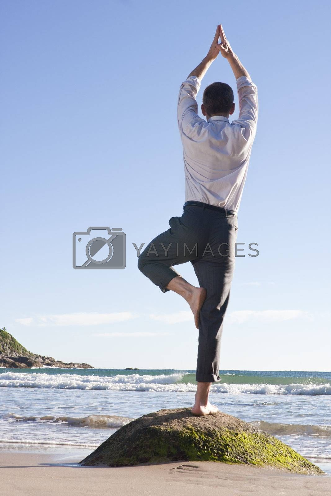Businessman doing equilibration exercise on a rock at the beach