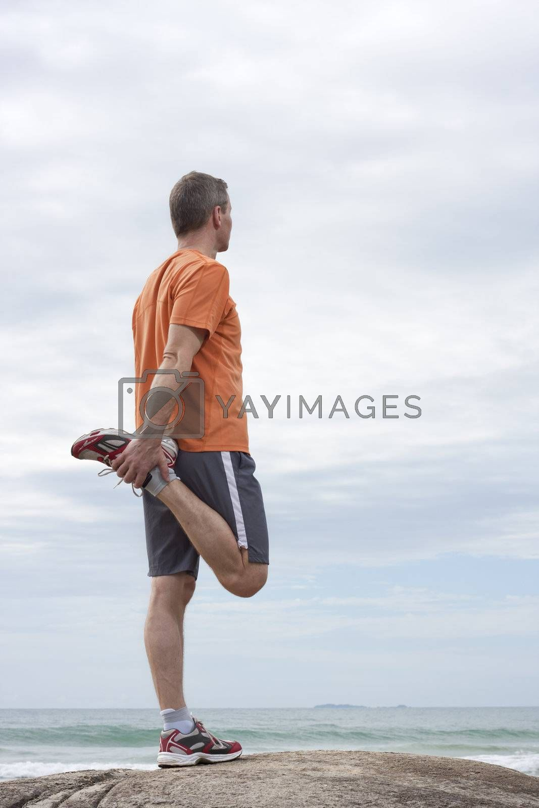Jogger doing stretching exercises on a beach