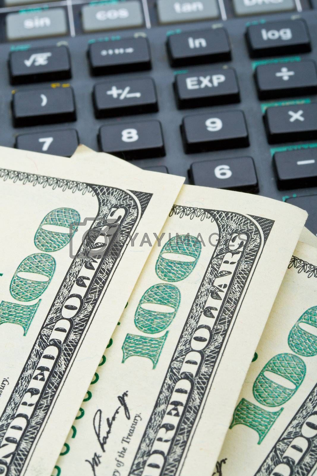 Royalty free image of many dollars over calculator by Alekcey