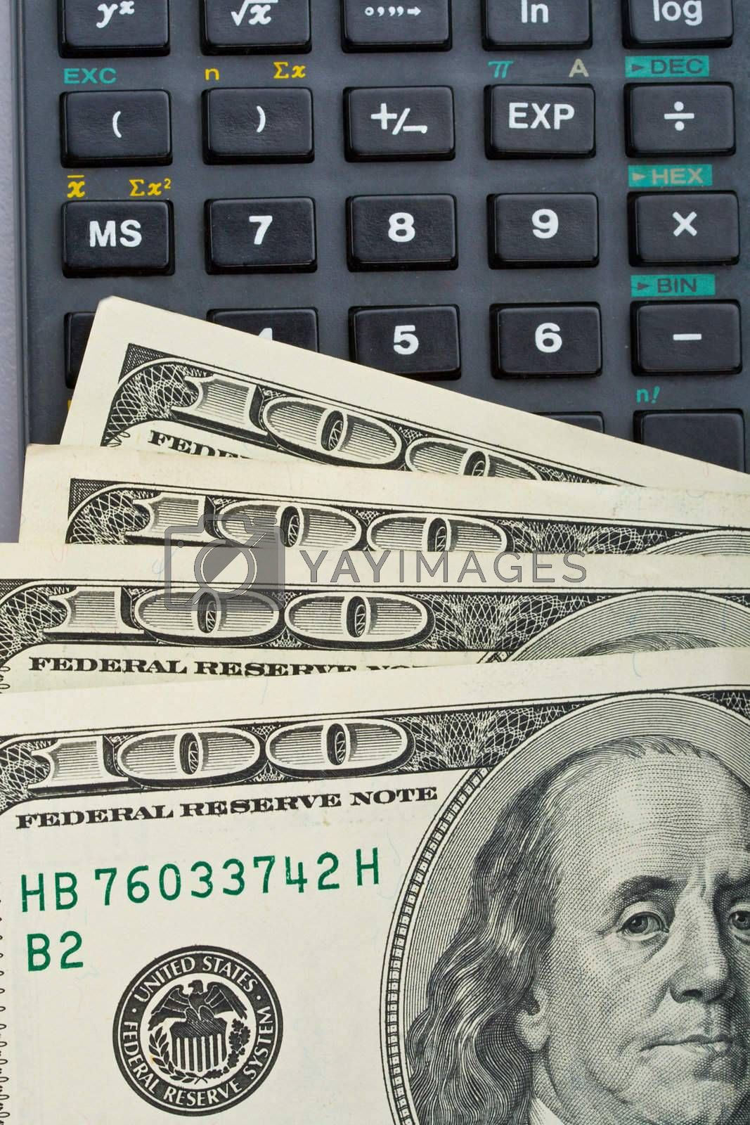 Royalty free image of many us dollars over calculator by Alekcey