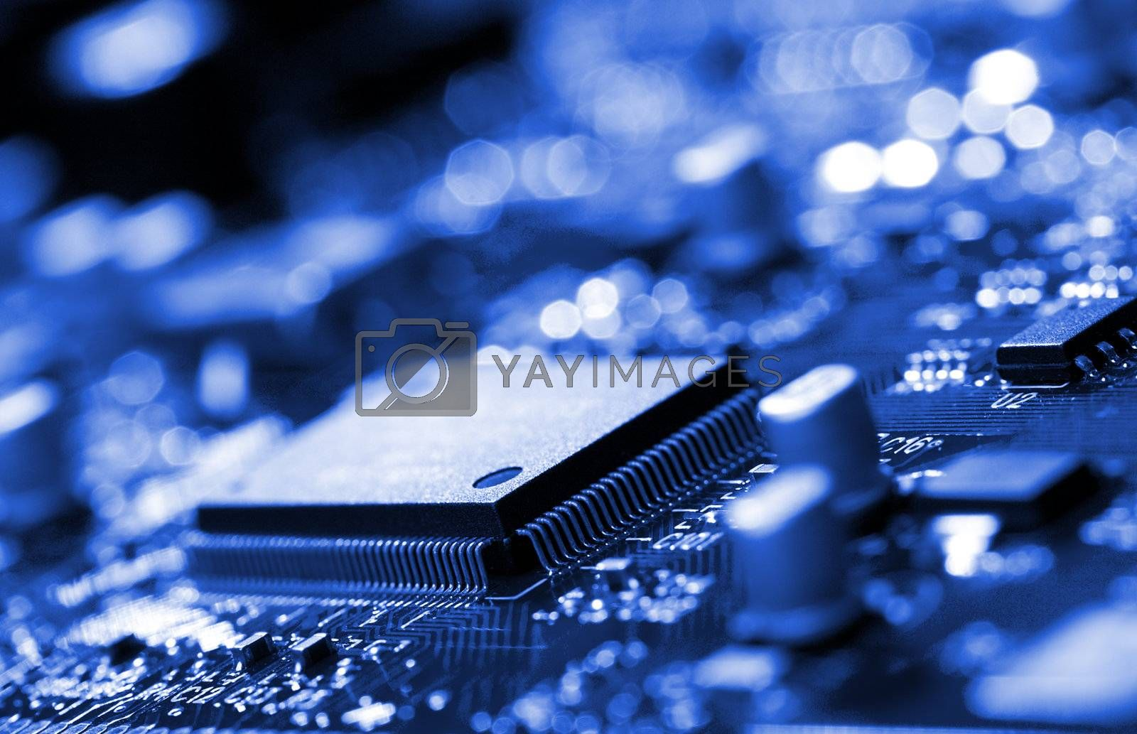 Royalty free image of microchip on blue circuit board by Alekcey