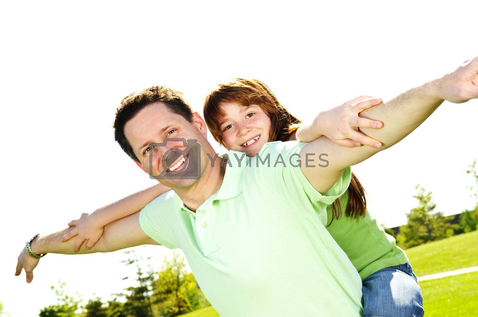 Portrait of happy father giving piggyback ride to child