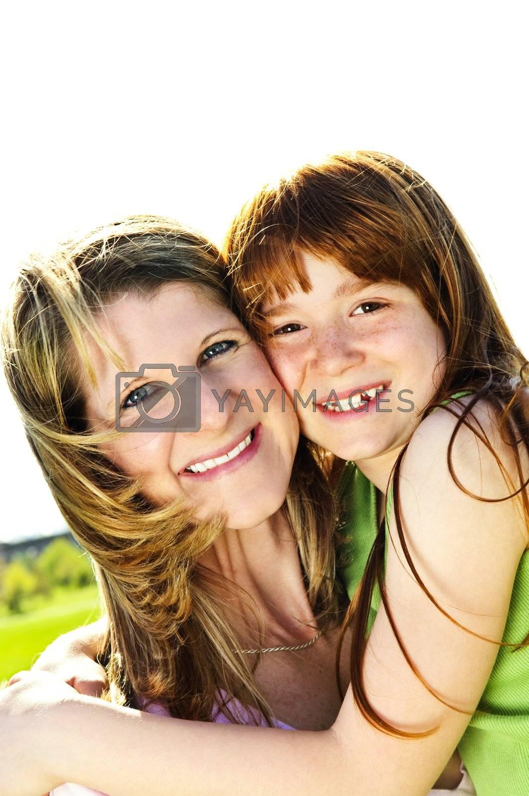 Portrait of happy child hugging her mother