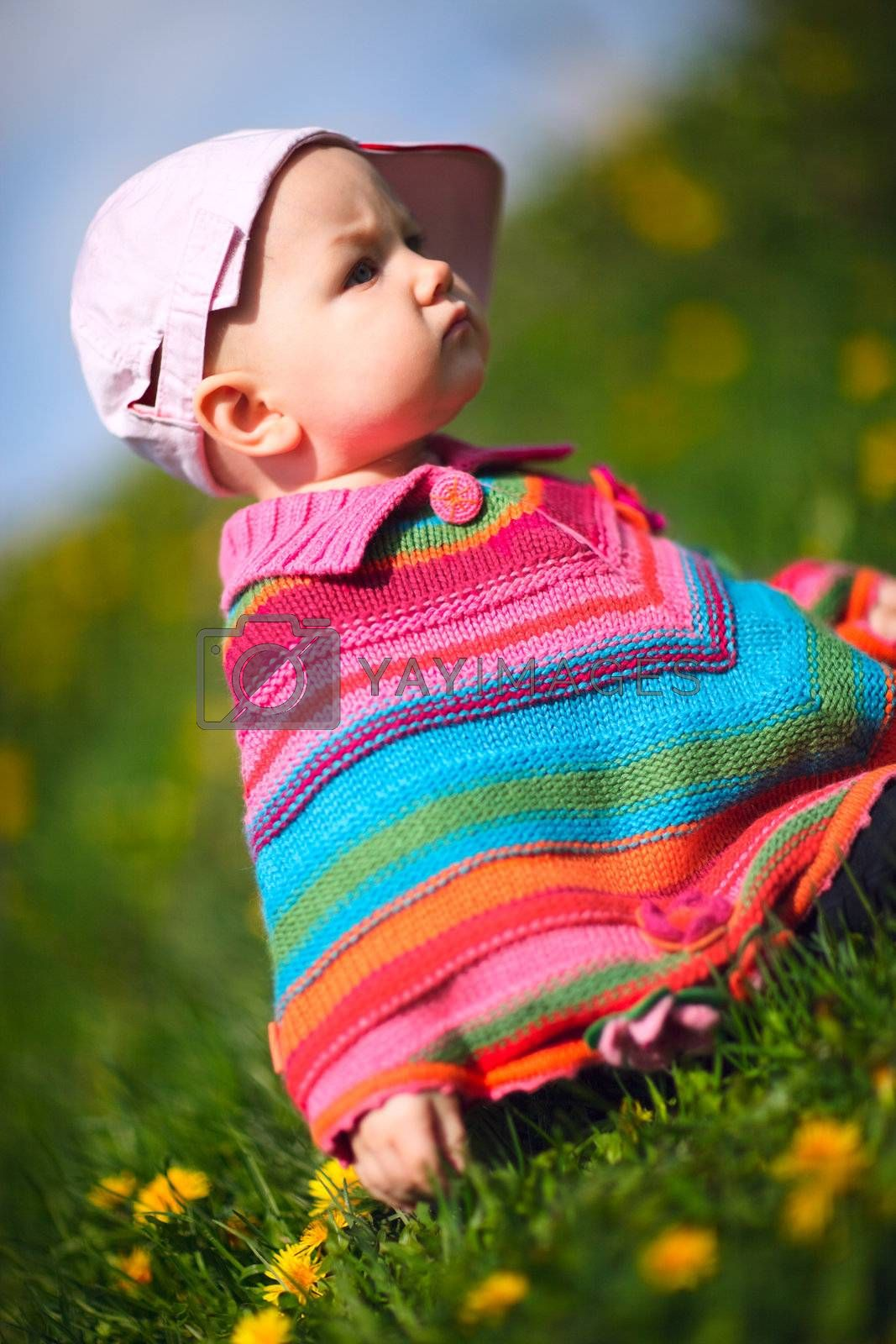 Cute baby girl sitting on grass