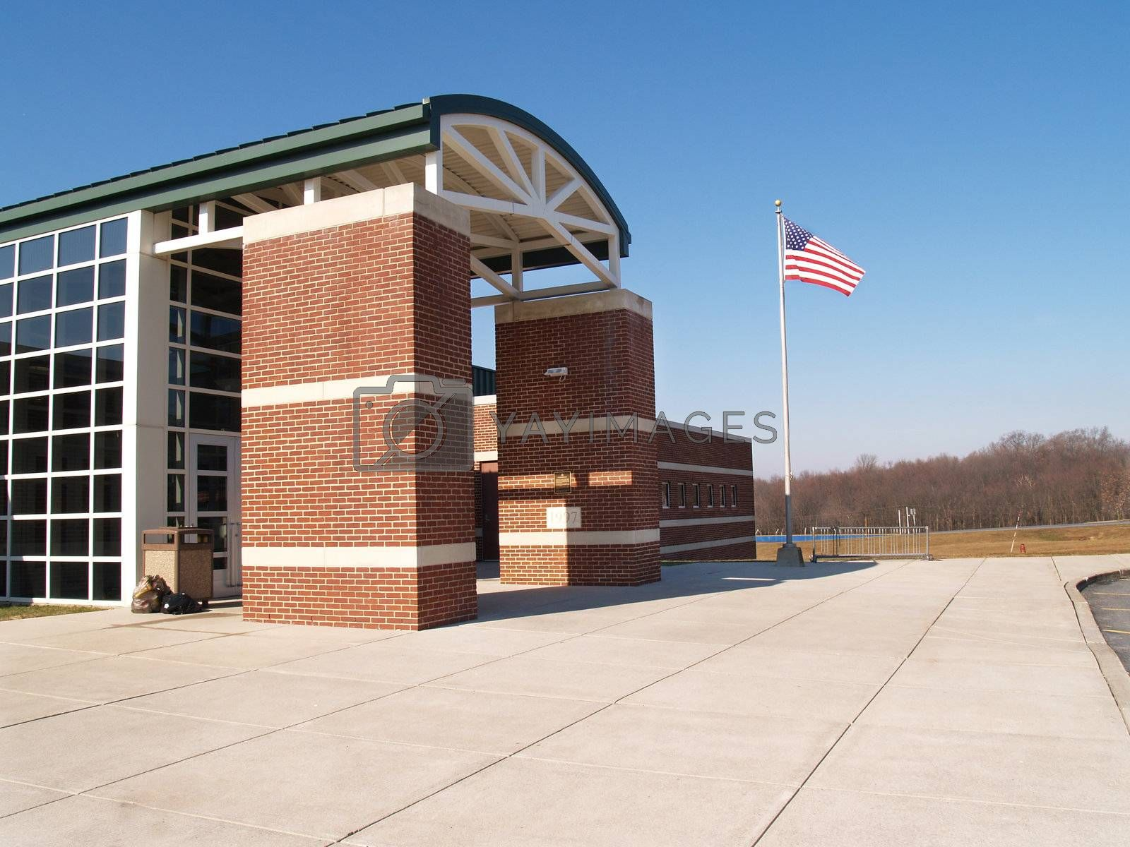 exterior of a red brick modern building with an American flag