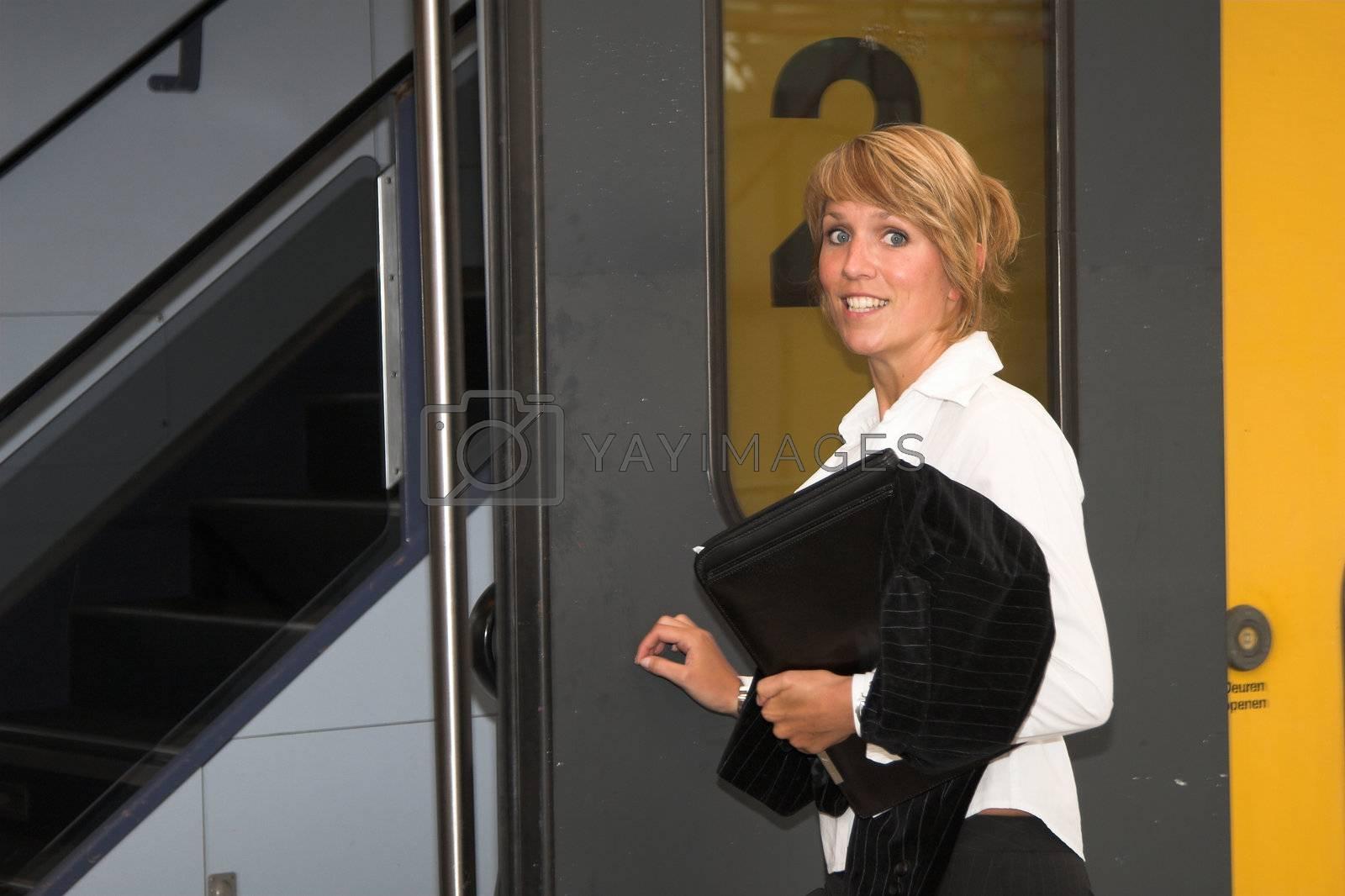 Pretty businesswoman getting on the train