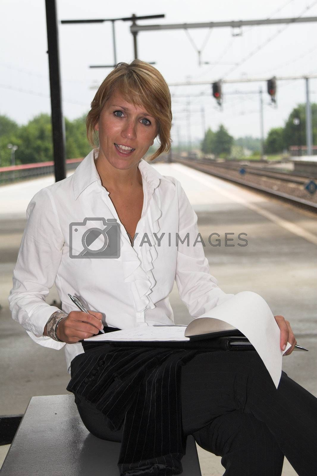 Businesswoman working at the station while waiting for the train to arrive