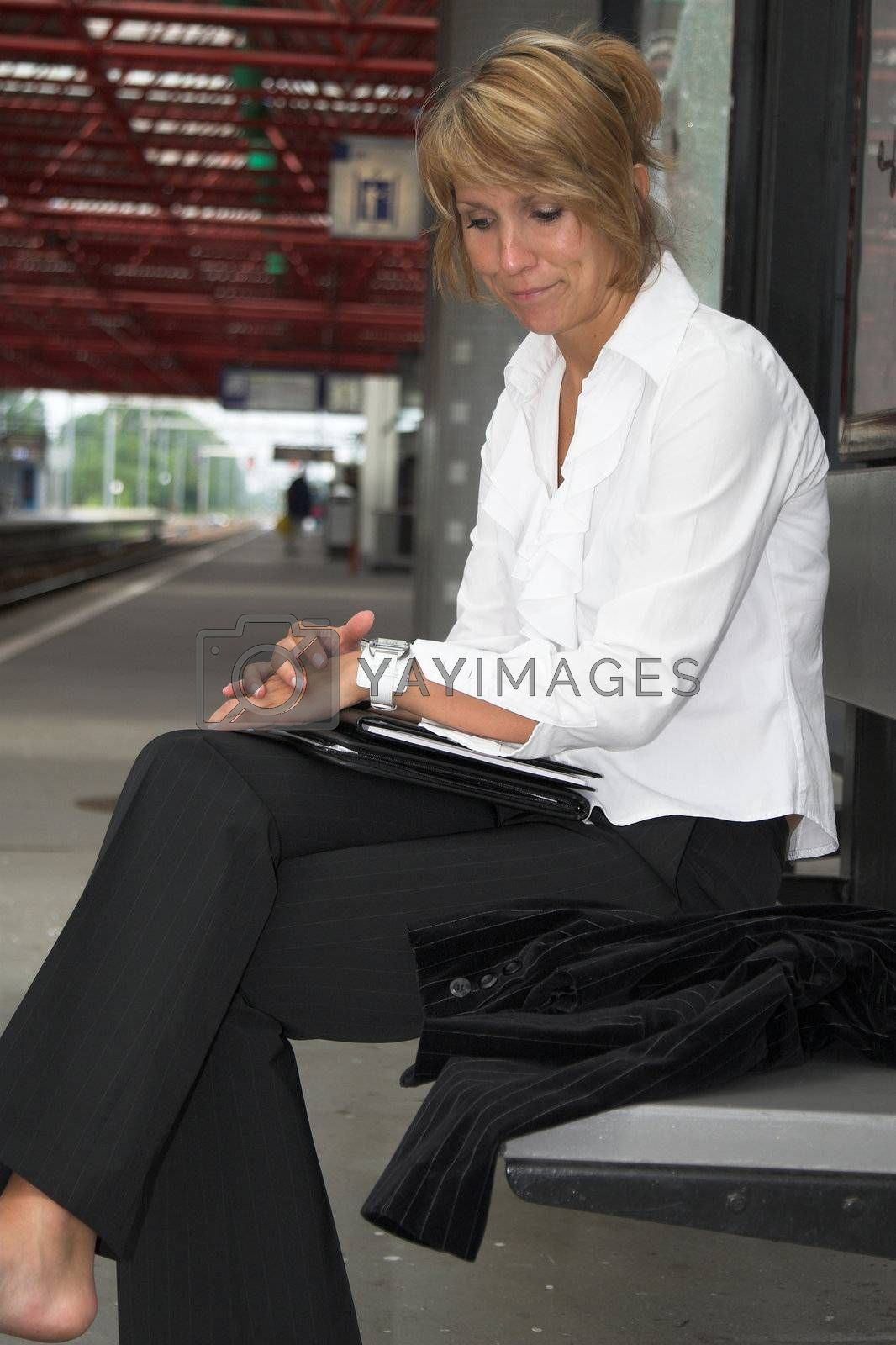 Businesswoman pulling an irritated face while waiting for the train