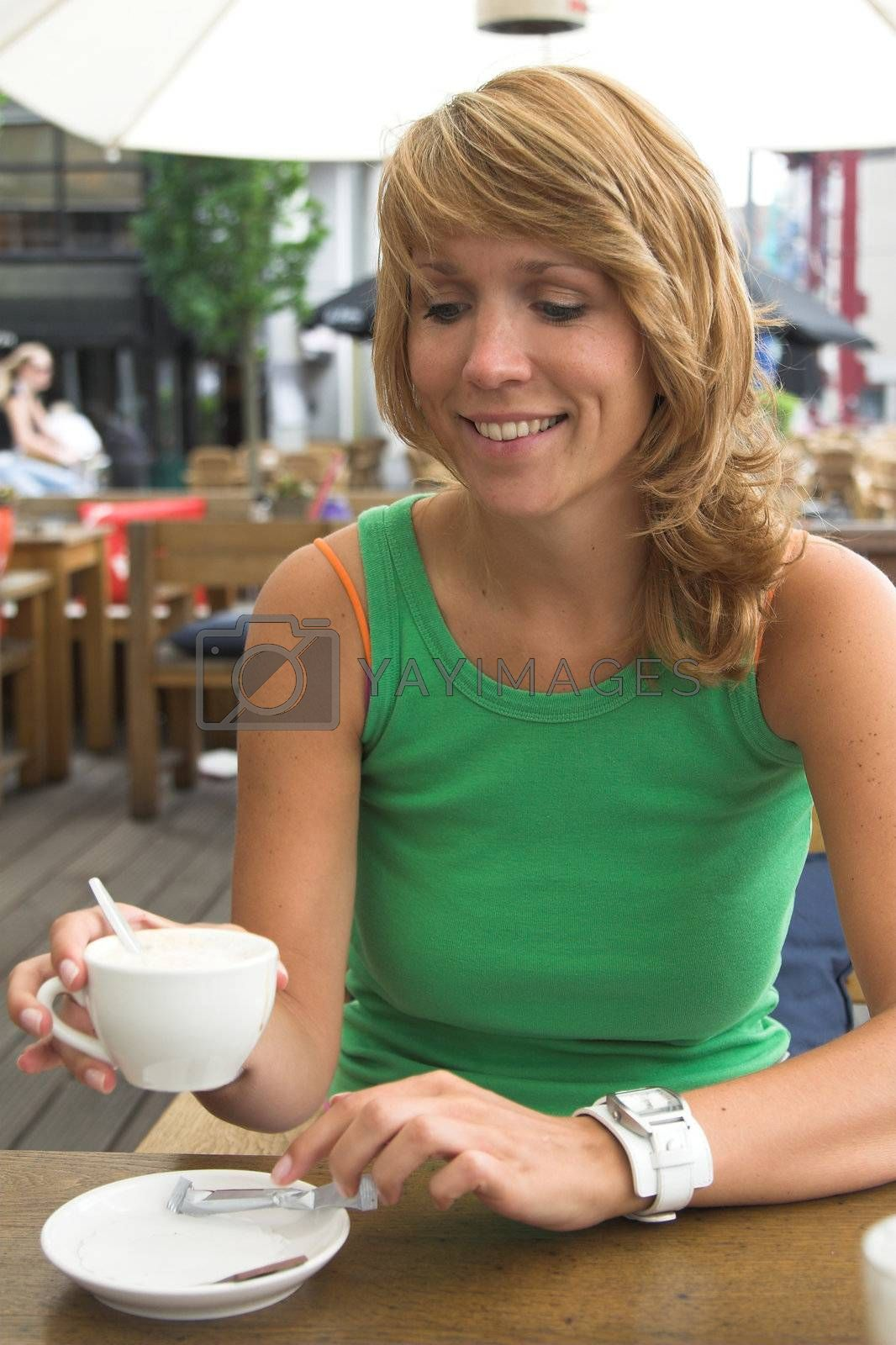 Pretty blond girl enjoying a cup of coffee on the terrace
