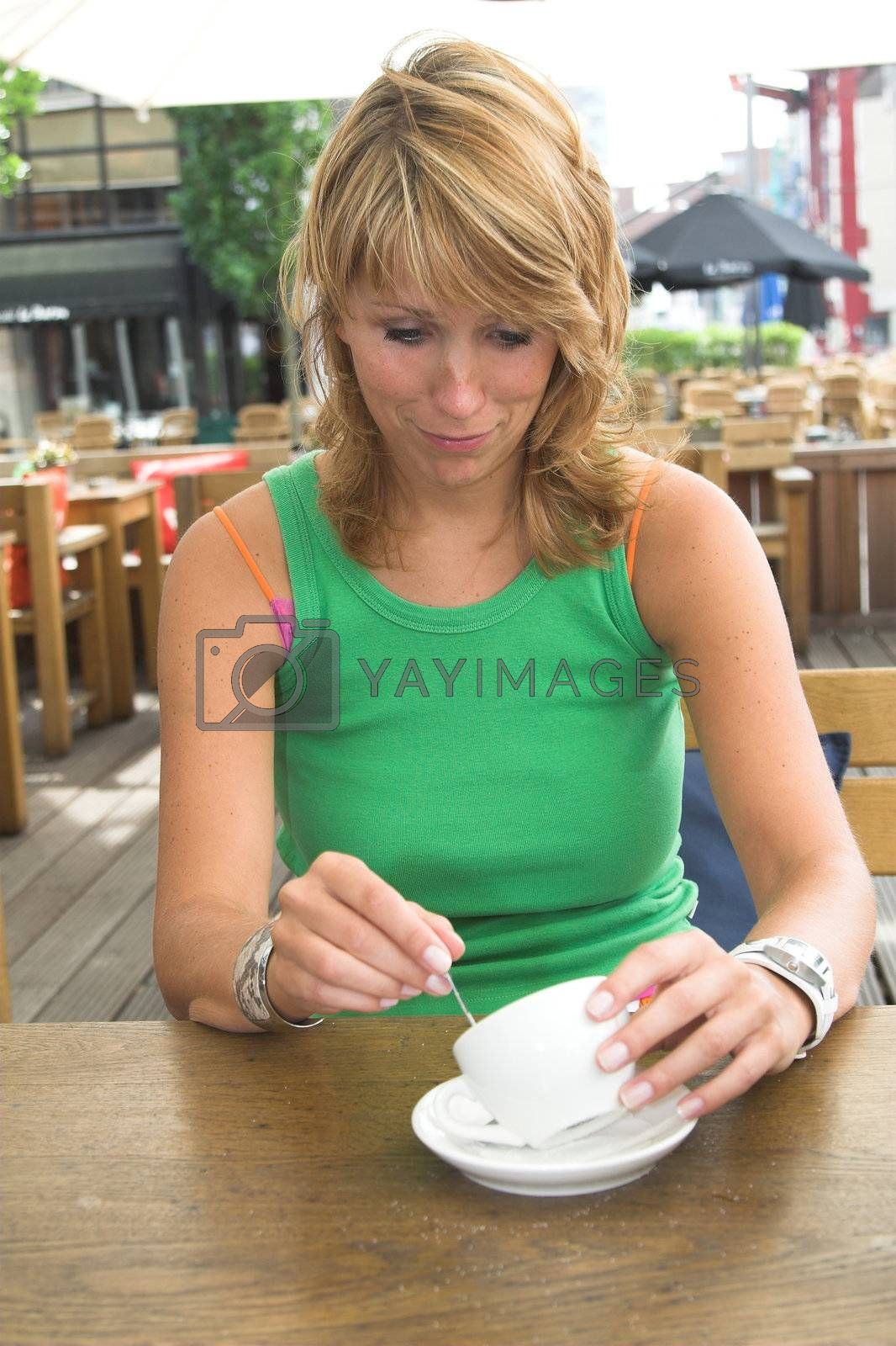 Pretty blond girl pulling a face because her coffeecup is empty
