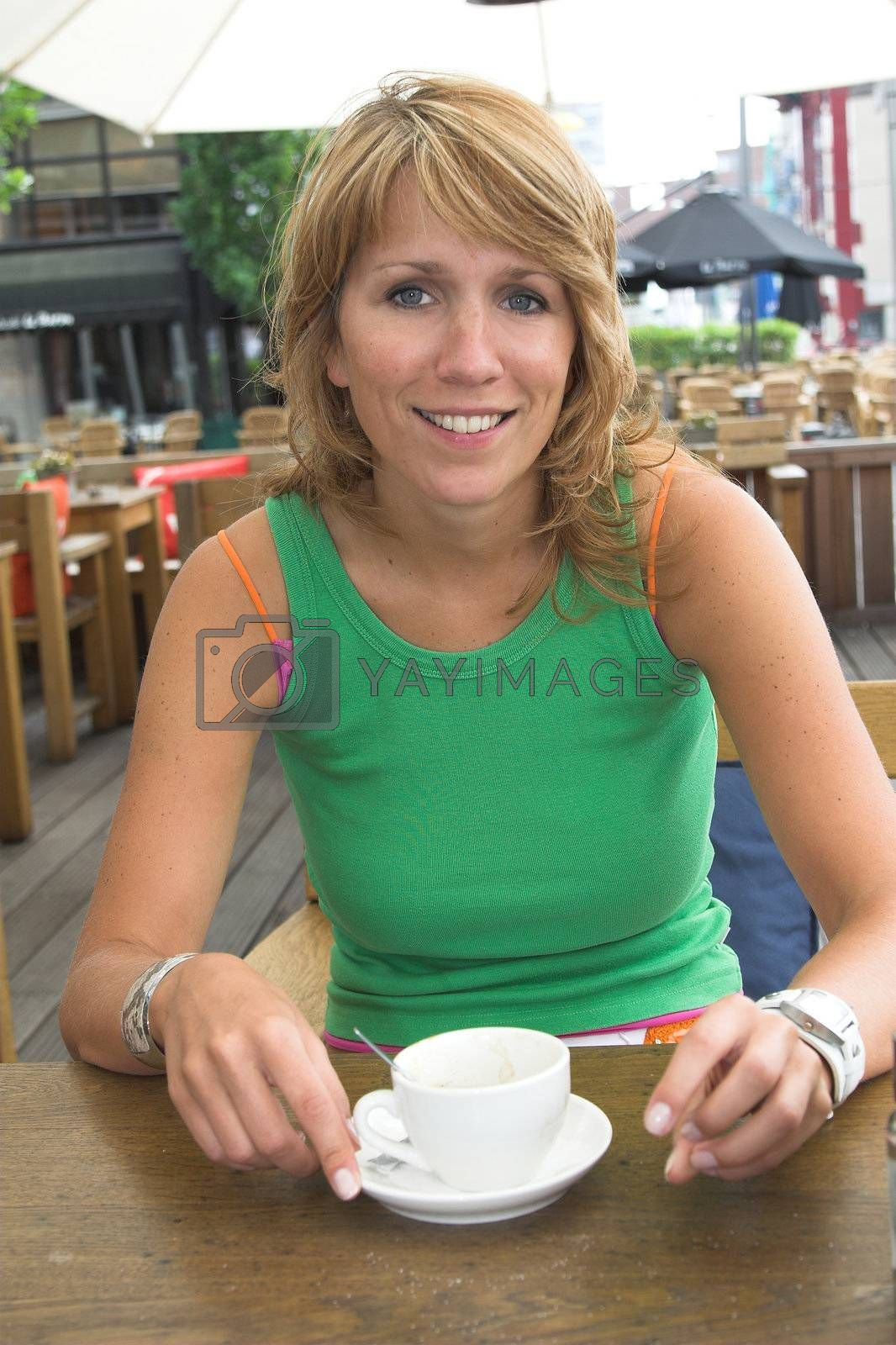 Pretty blond girl enjoying a coffee on the terrace