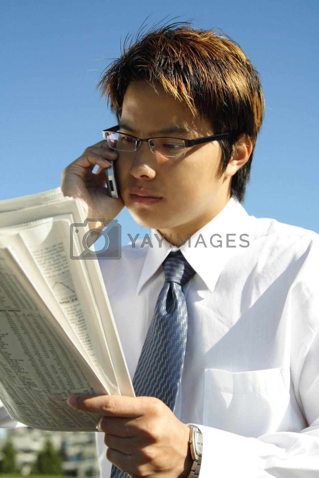Businessman reading a financial newspaper while making a phone call