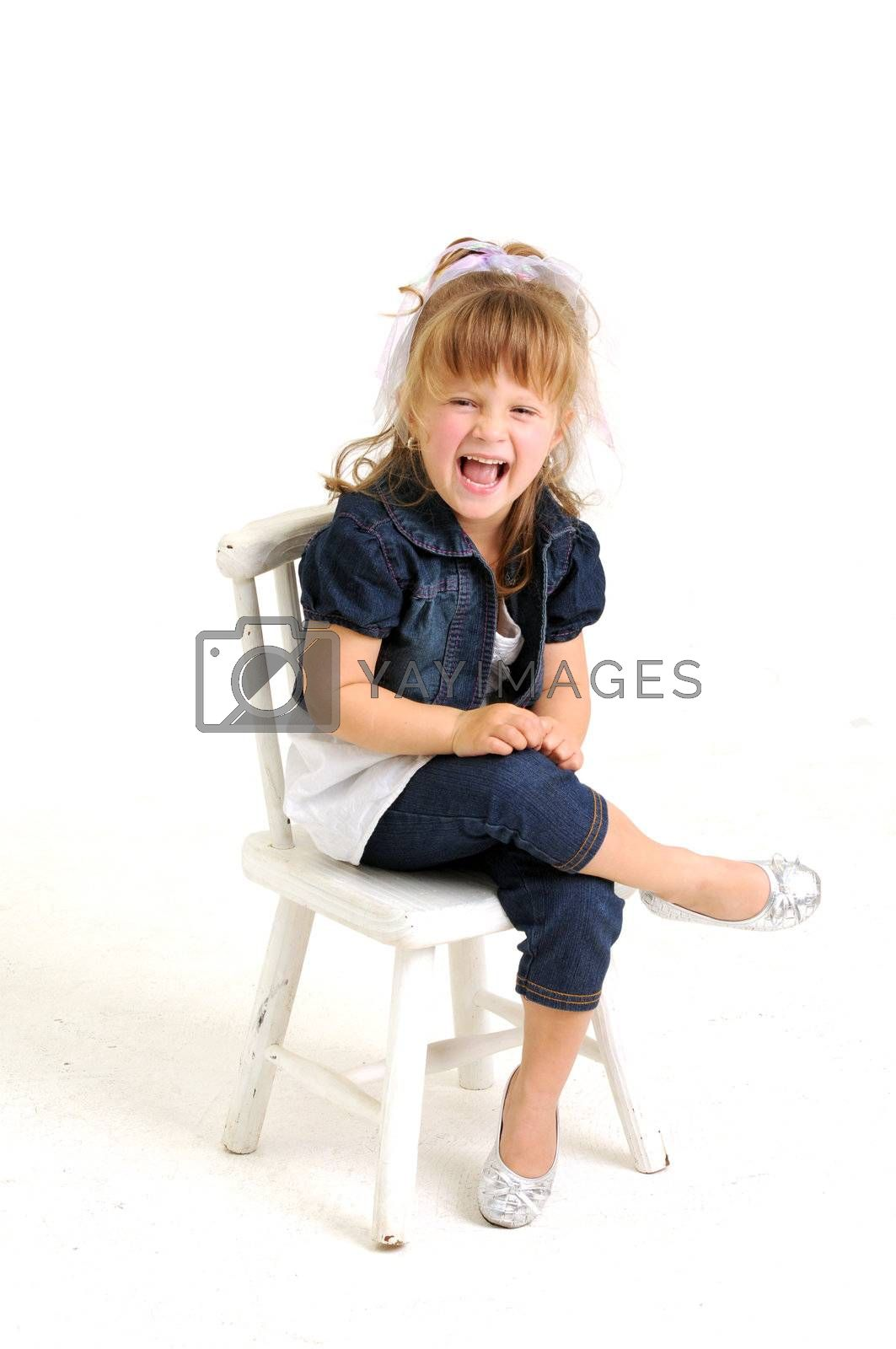 young pretty blond girl with blue dress sitting on a white chair and laughting