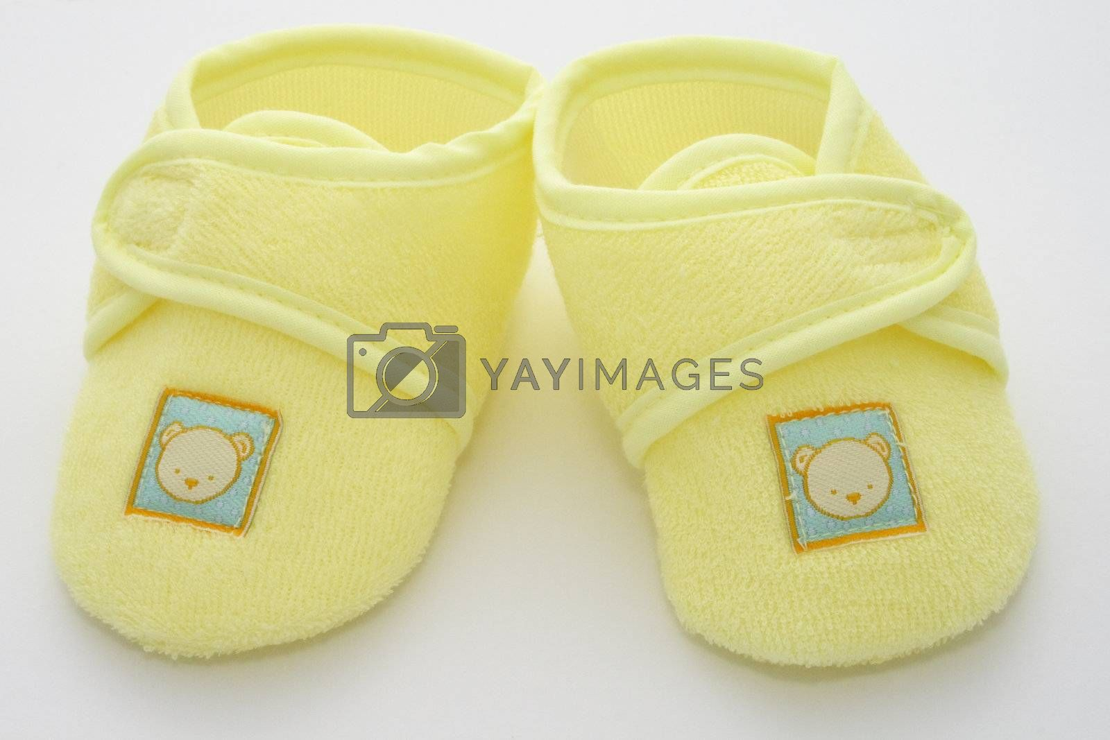 babies first pair of shoes in a yellow towelling material