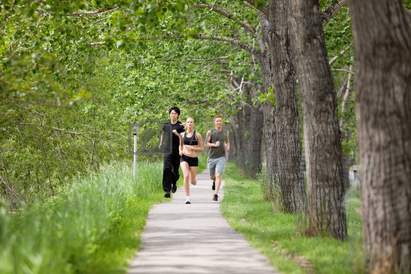 Young people running on walkway by trees