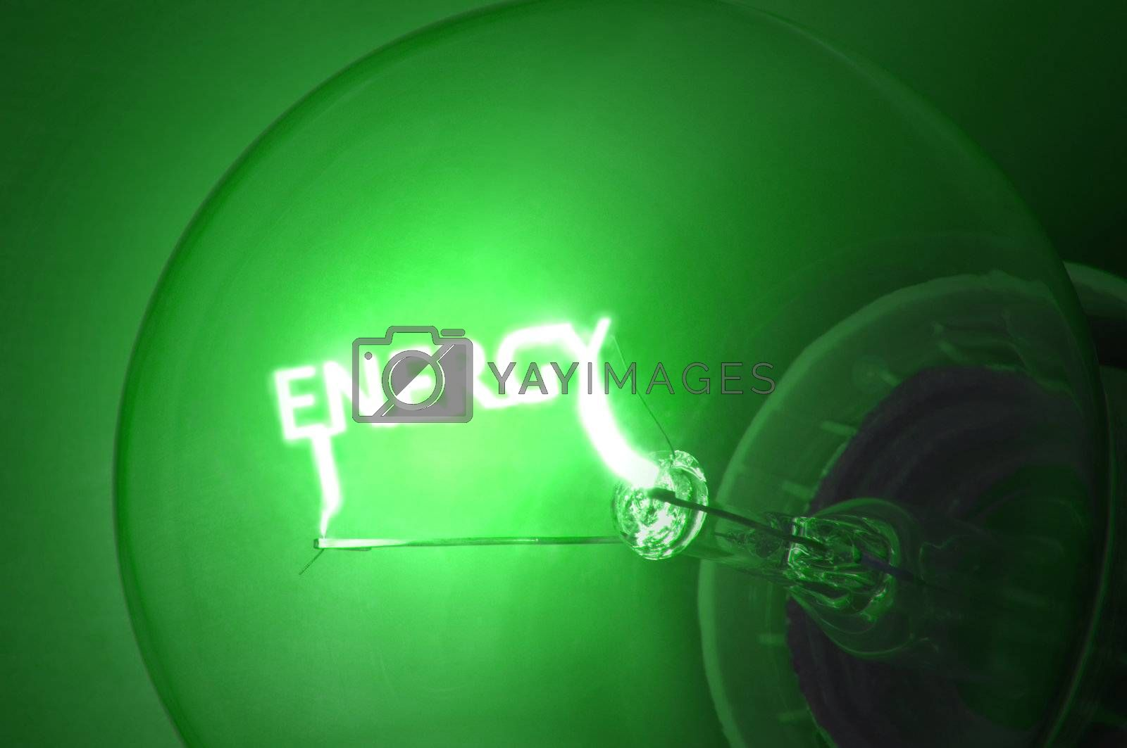 """Close up on illuminated green light bulb filament which spells the word """"ENERGY""""."""
