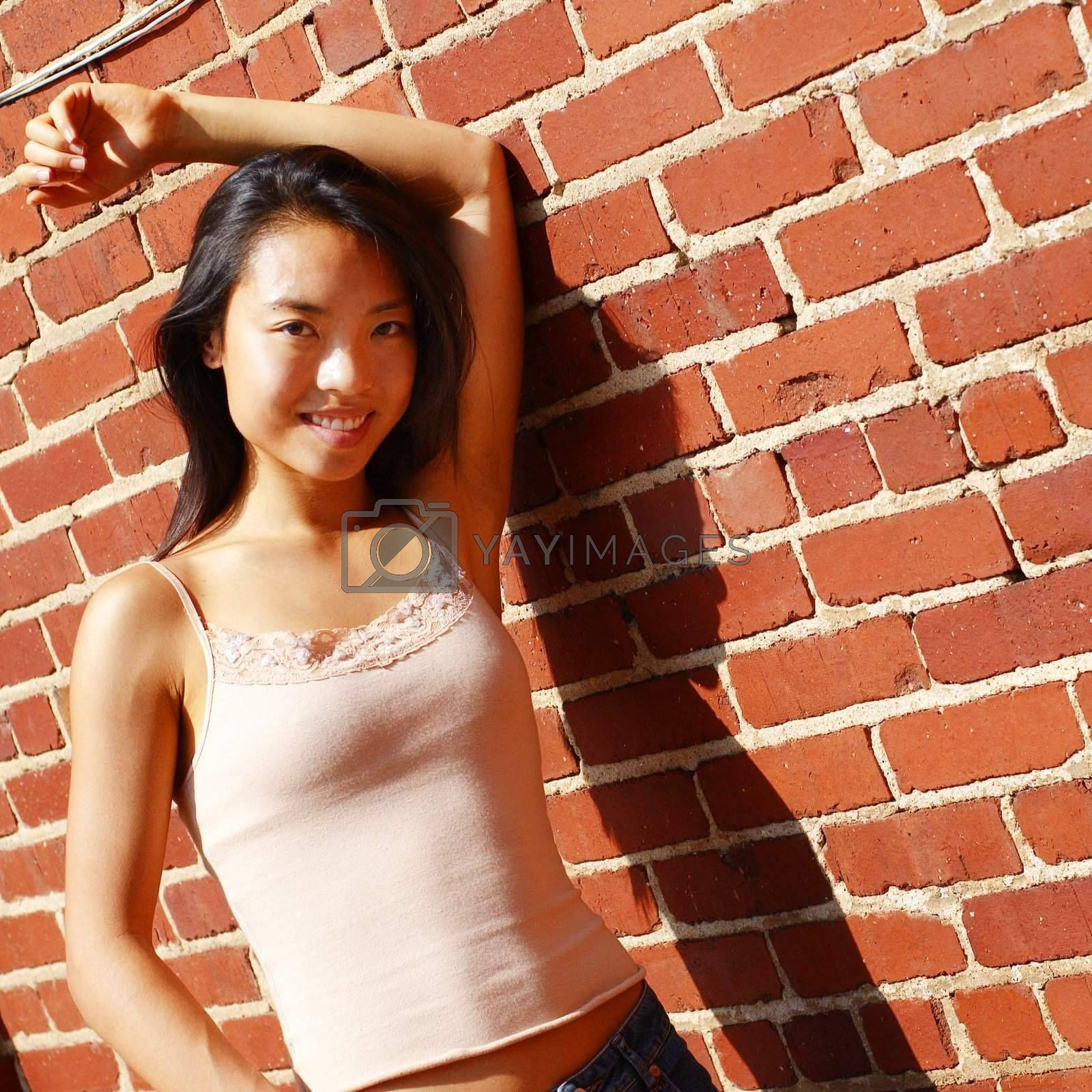 Fashionable young woman against red brick wall.