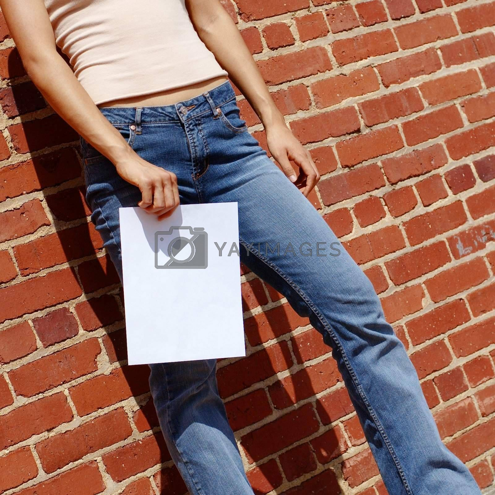 Fashionable girl against red brick wall with blank paper.