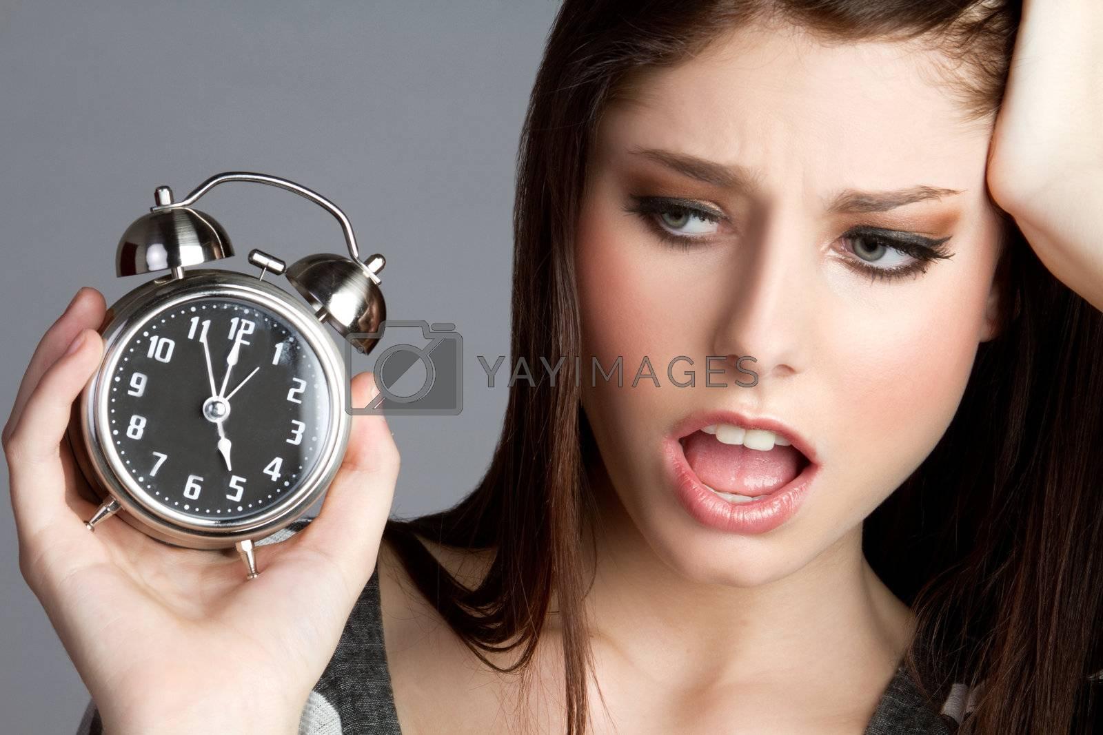 Annoyed woman holding alram clock