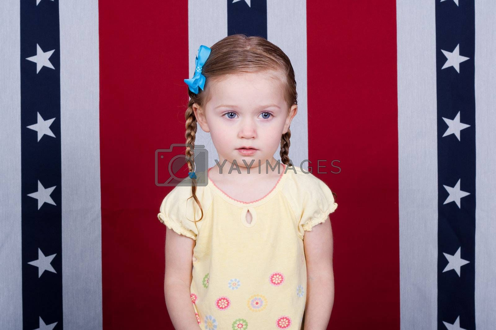 A confused child standing in front of an American Flag style background.