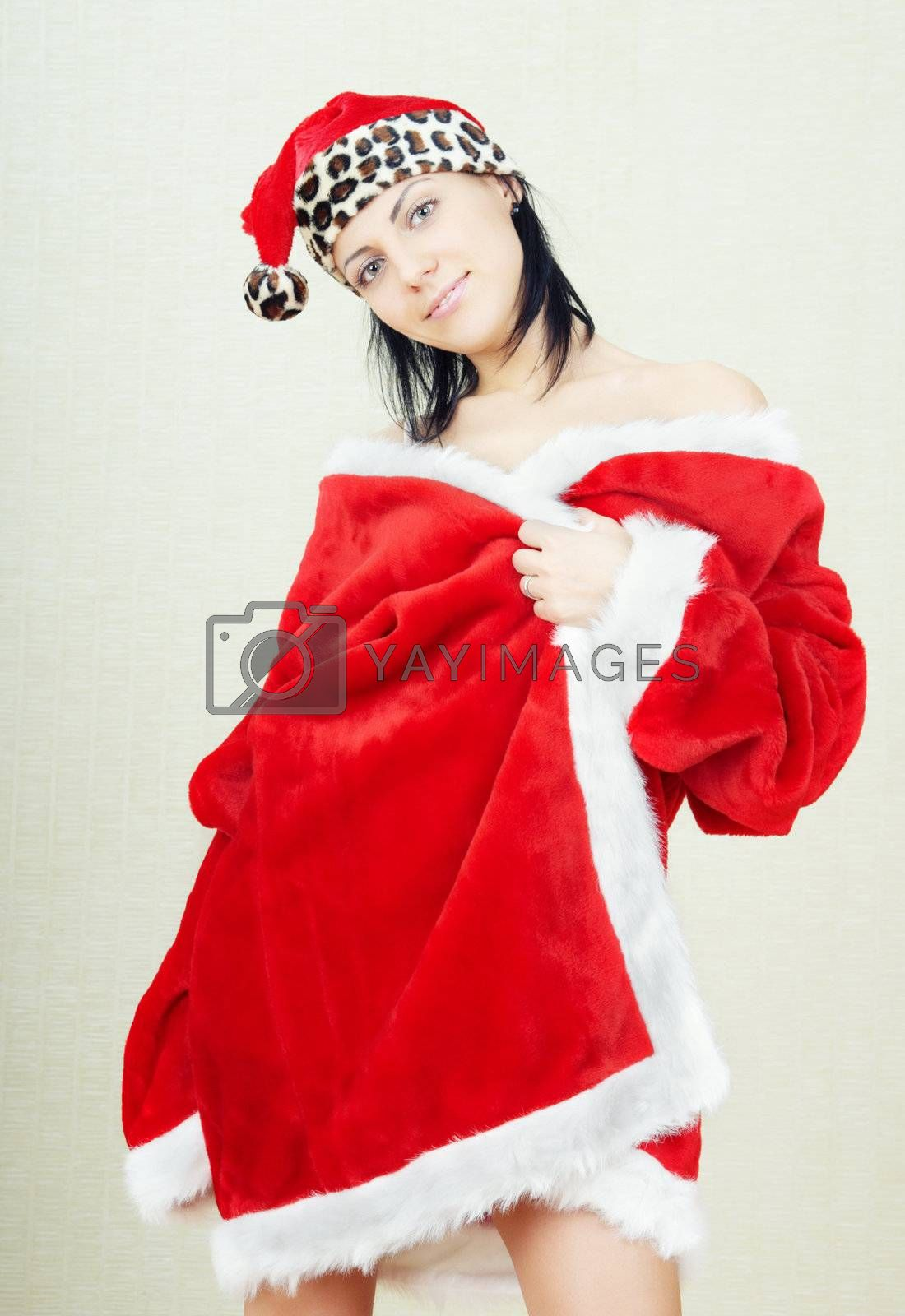 Smiling brunette lady indoors in the red furry Santa Claus dress and hat