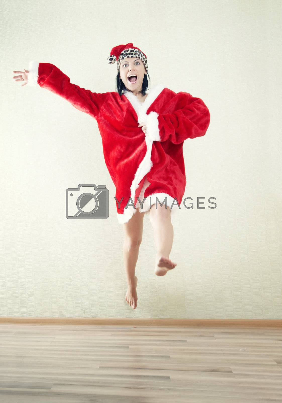 Jumping lady in the red Santa Claus costume indoors. Natural light and colors