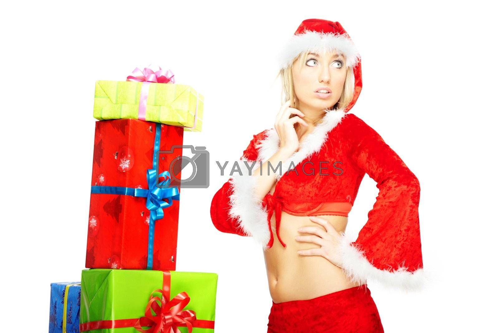 Attractive woman in the red Santa Claus costume posing near the numerous gift boxes on a white background