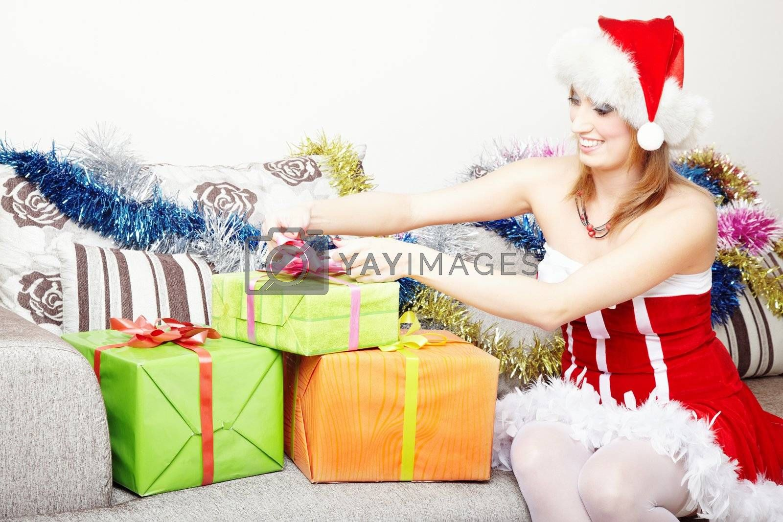 Smiling lady in the red furry Santa Claus costume and hat preparing Christmas gifts