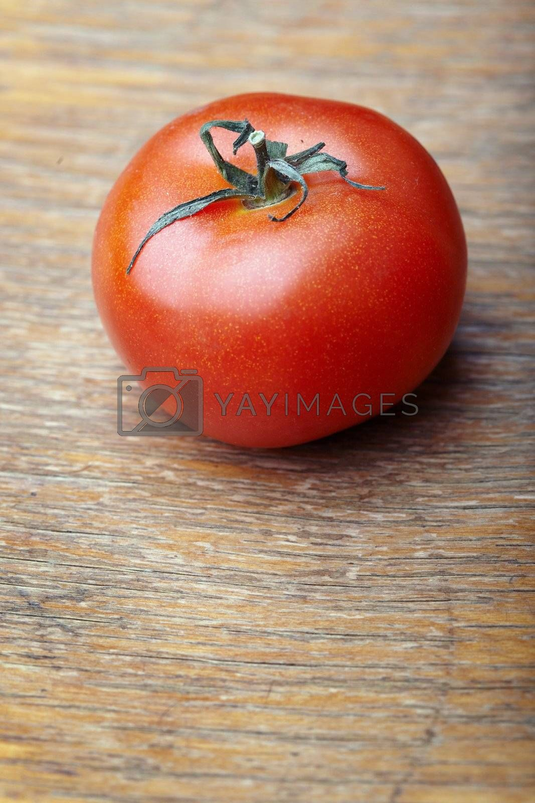 Close-up photo of the red tomato of the wooden background. Shallow depth of field added for natural view