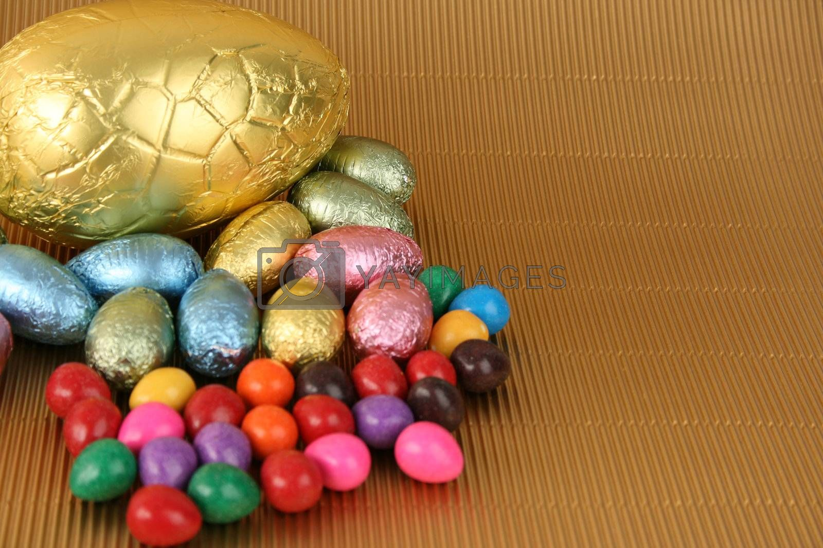 Various colors and shaped easter eggs on a gold background