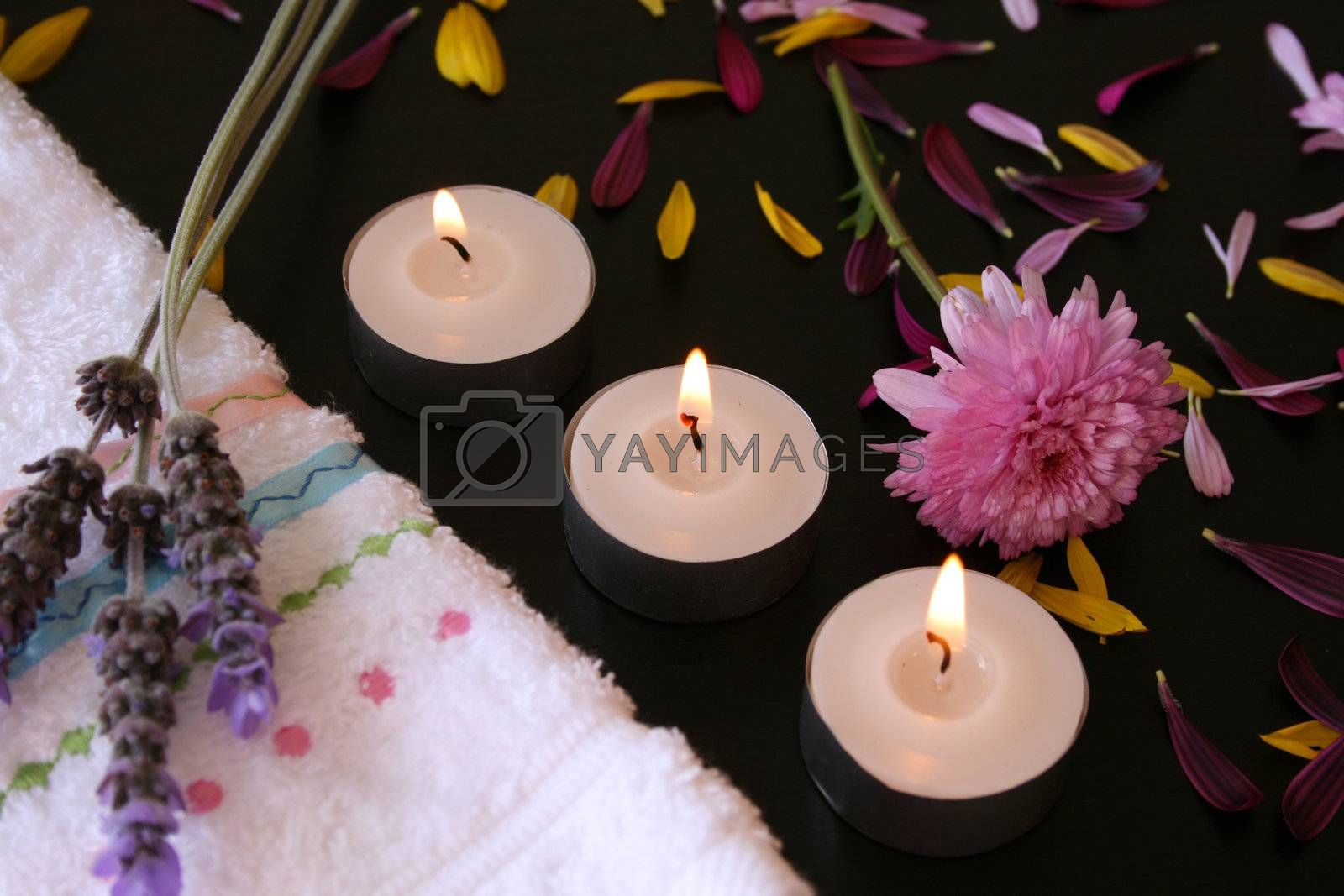Three teelights next to a hand towel with fresh flowers and petals