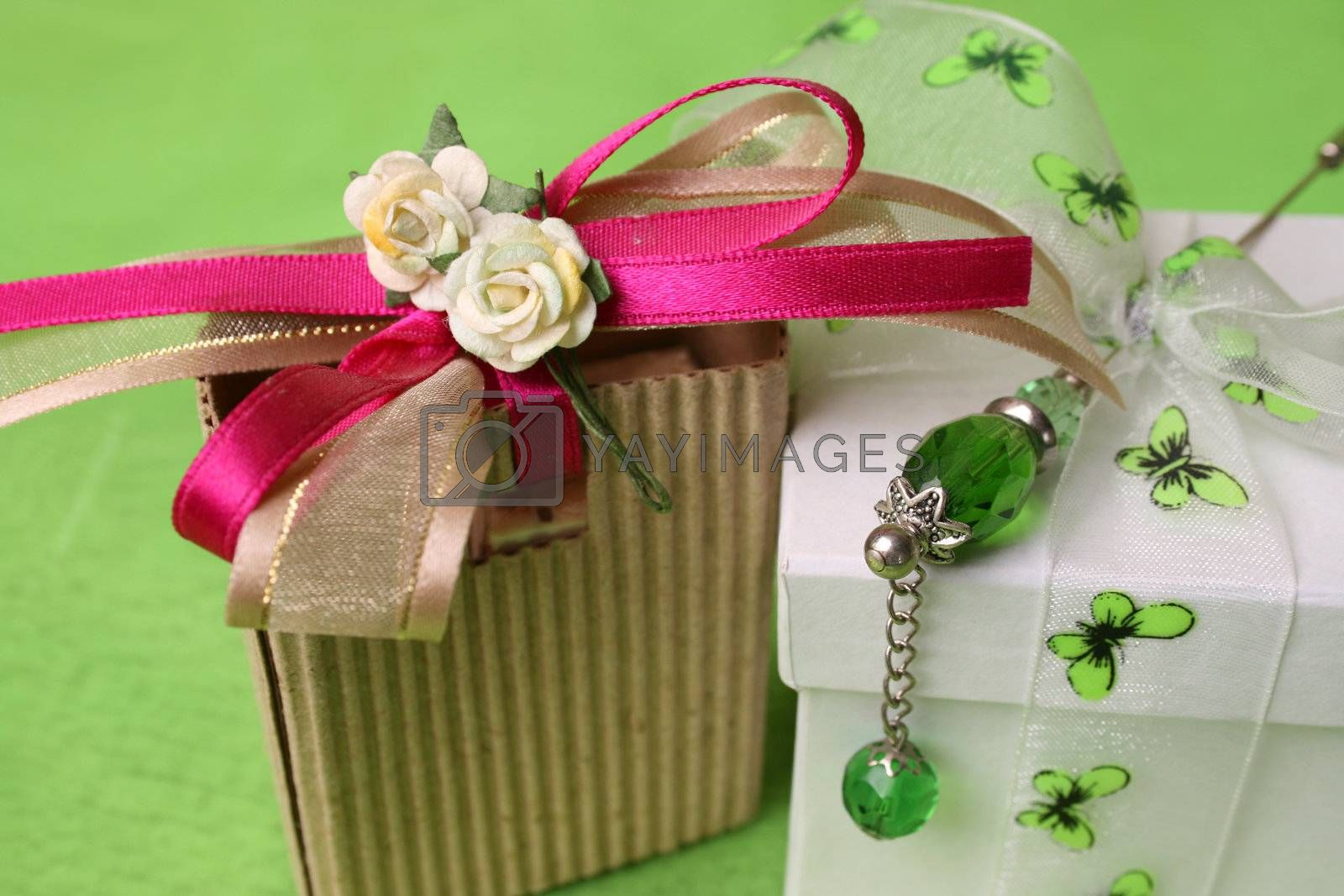 White gift box and small brown gift bag with ribbons