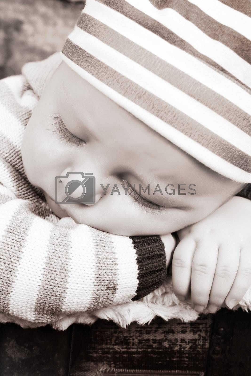 Beautiful baby boy sleeping in an antique trunk