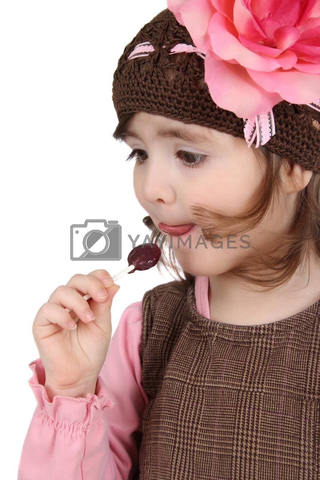 Cute brunette toddler earing a lollipop against white background
