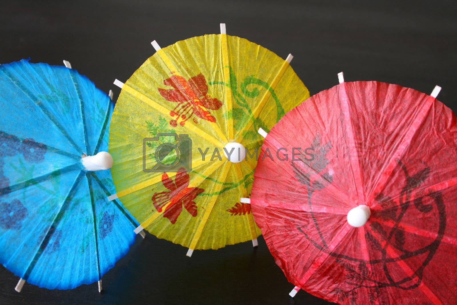 Blue, yellow and red Cocktail Umbrellas on a dark surface