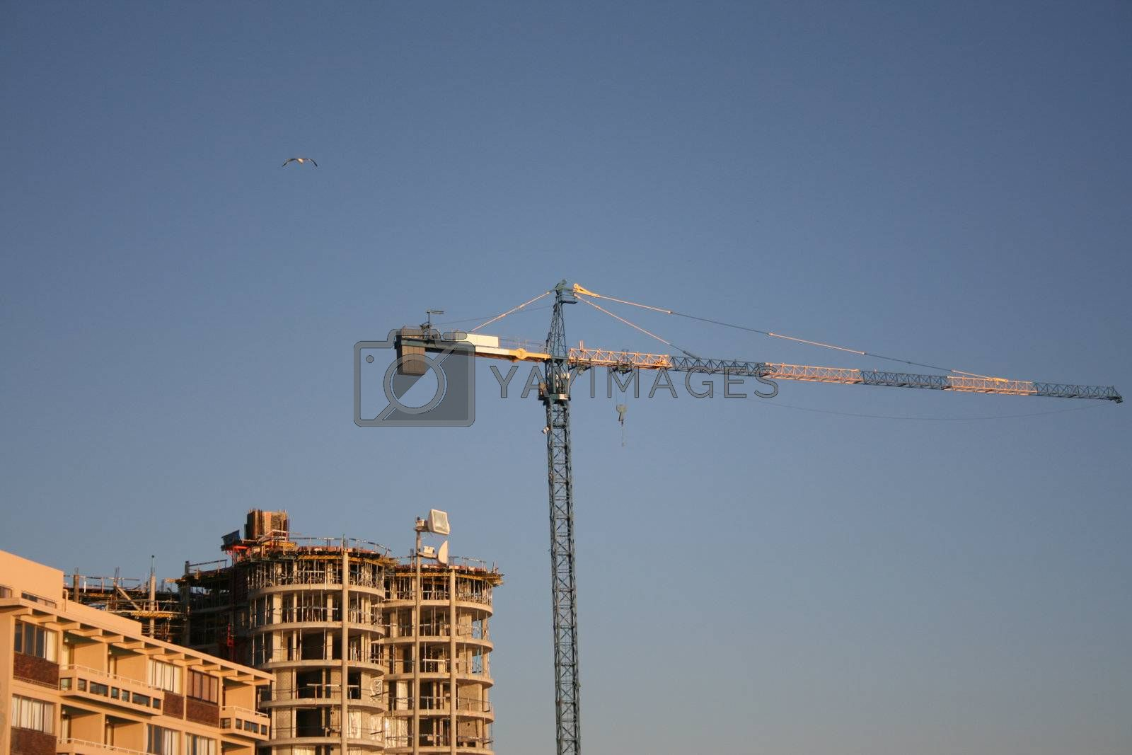 High Crane against a blue sky close to a building site Building Crane behind other buildings with construction to the right