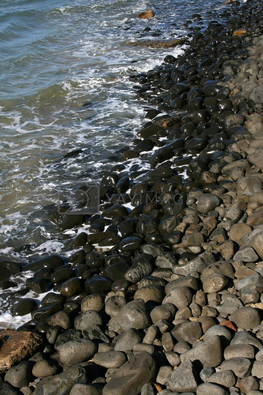Half dry half wet pebbles with water ebb and flow
