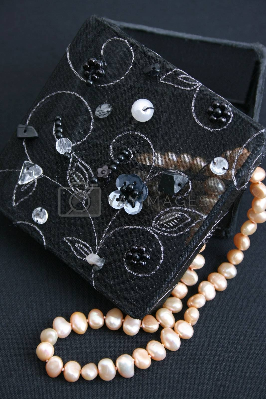 Black embroidered jewelery box with a string of pearls
