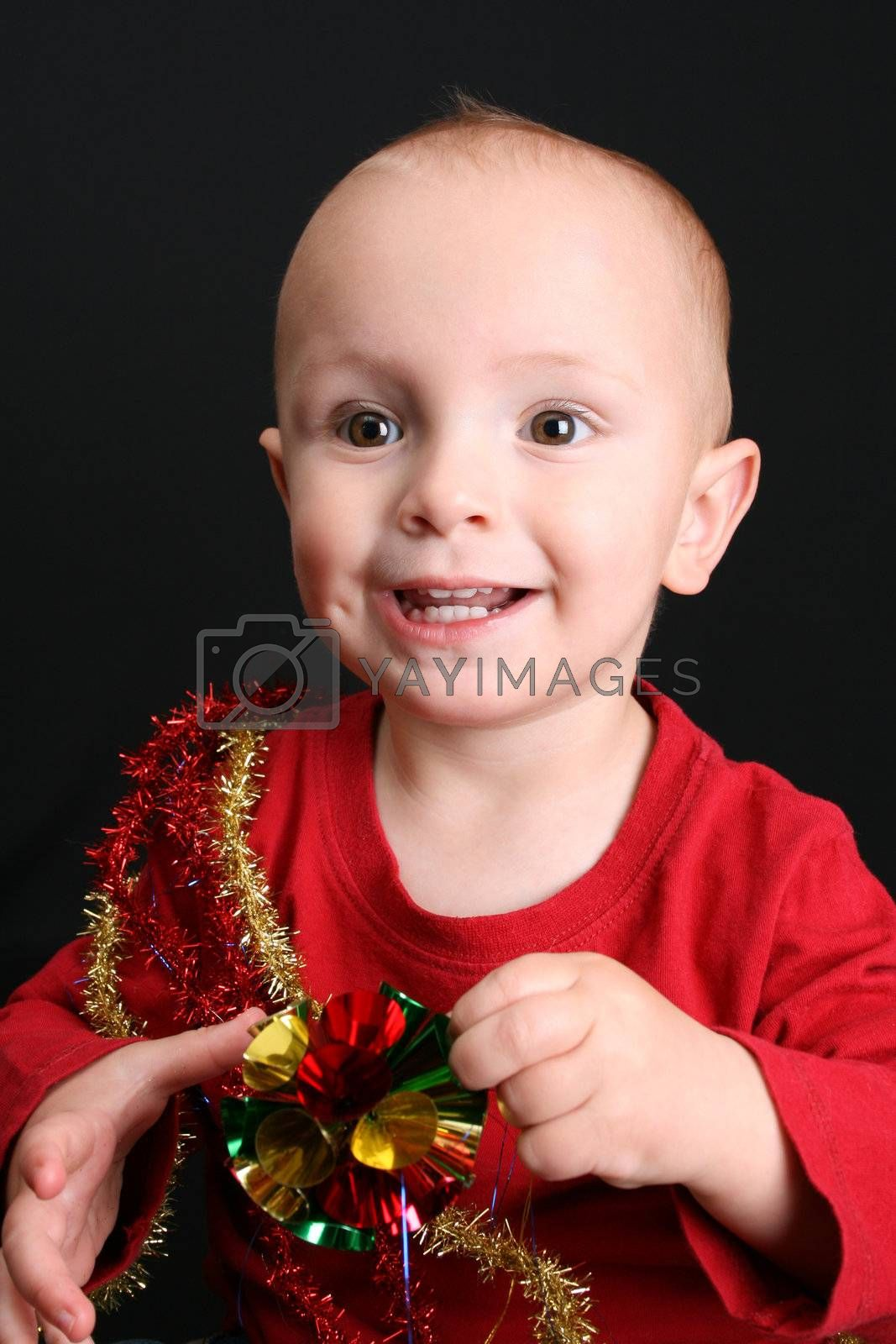 Toddler against a black background playing with christmas decorations