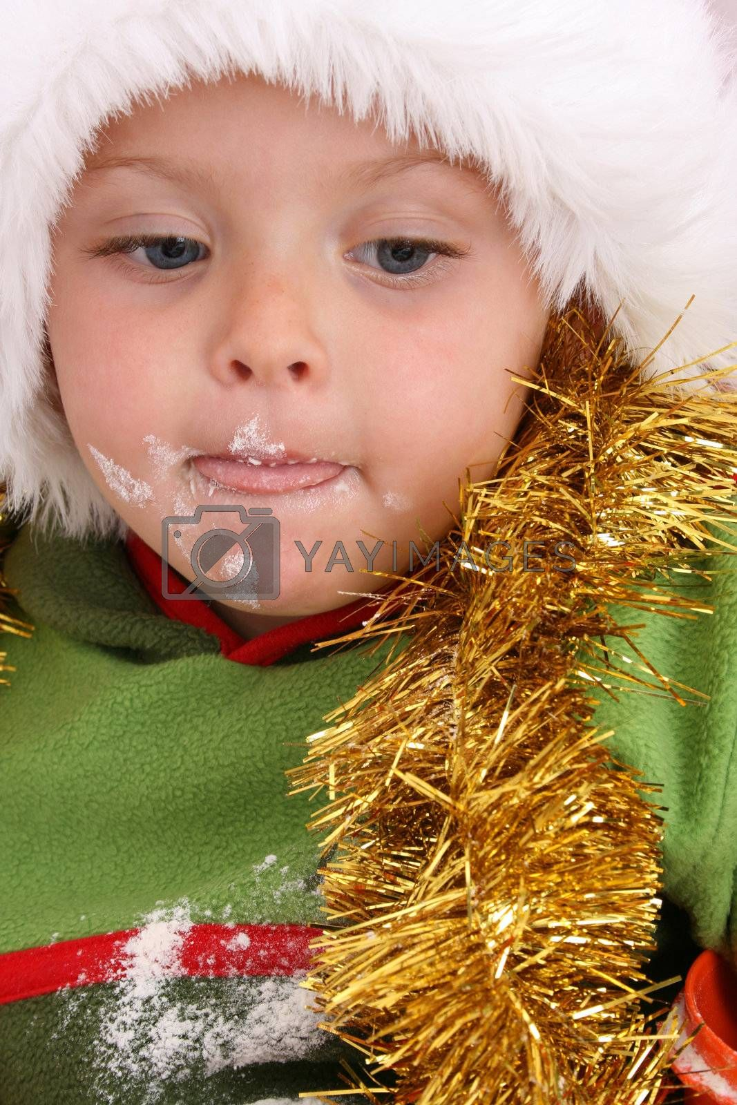 Toddler wearing a christmas hat, baking christmas cookies