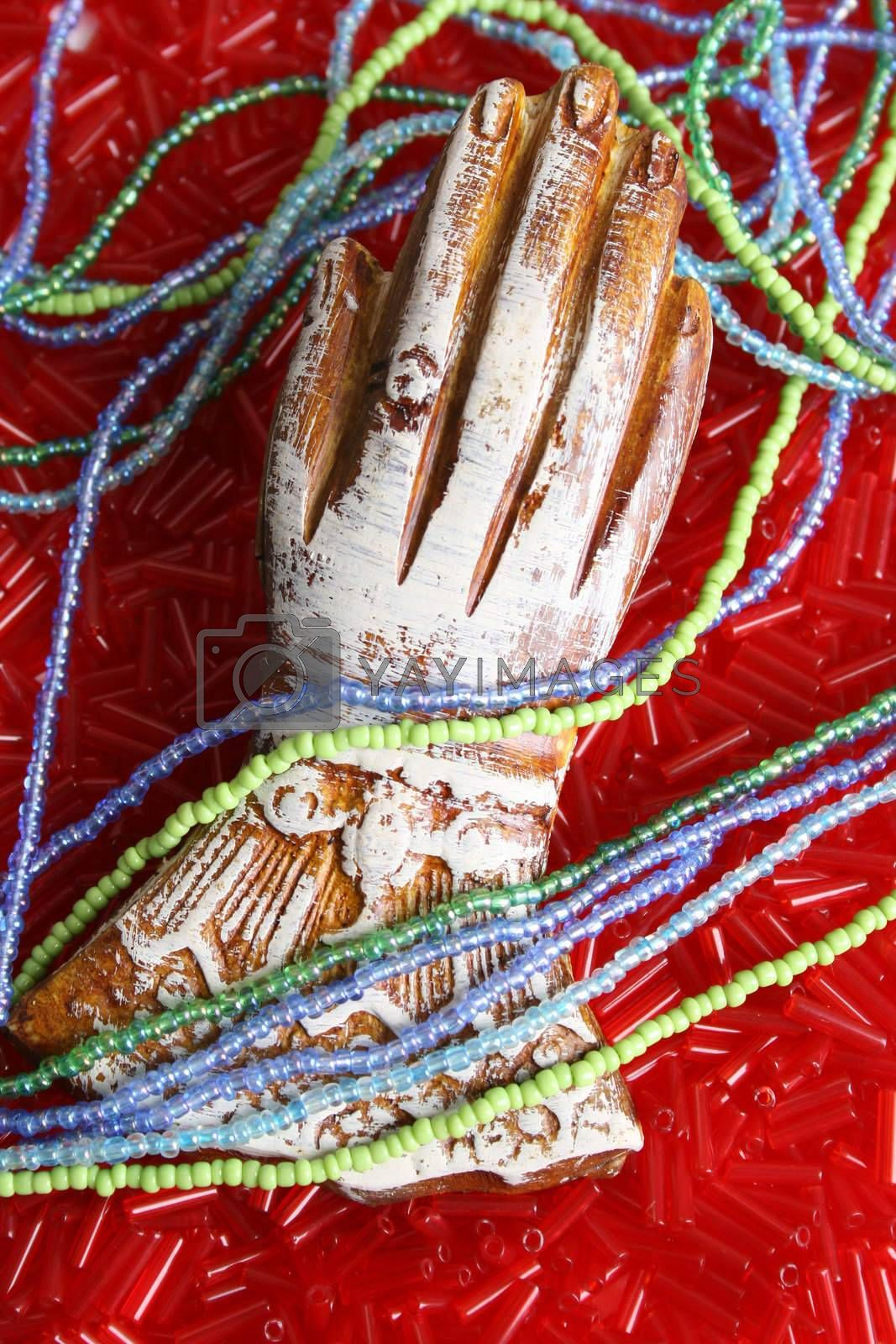 Ornate wooden hand on a bed of beads with strings