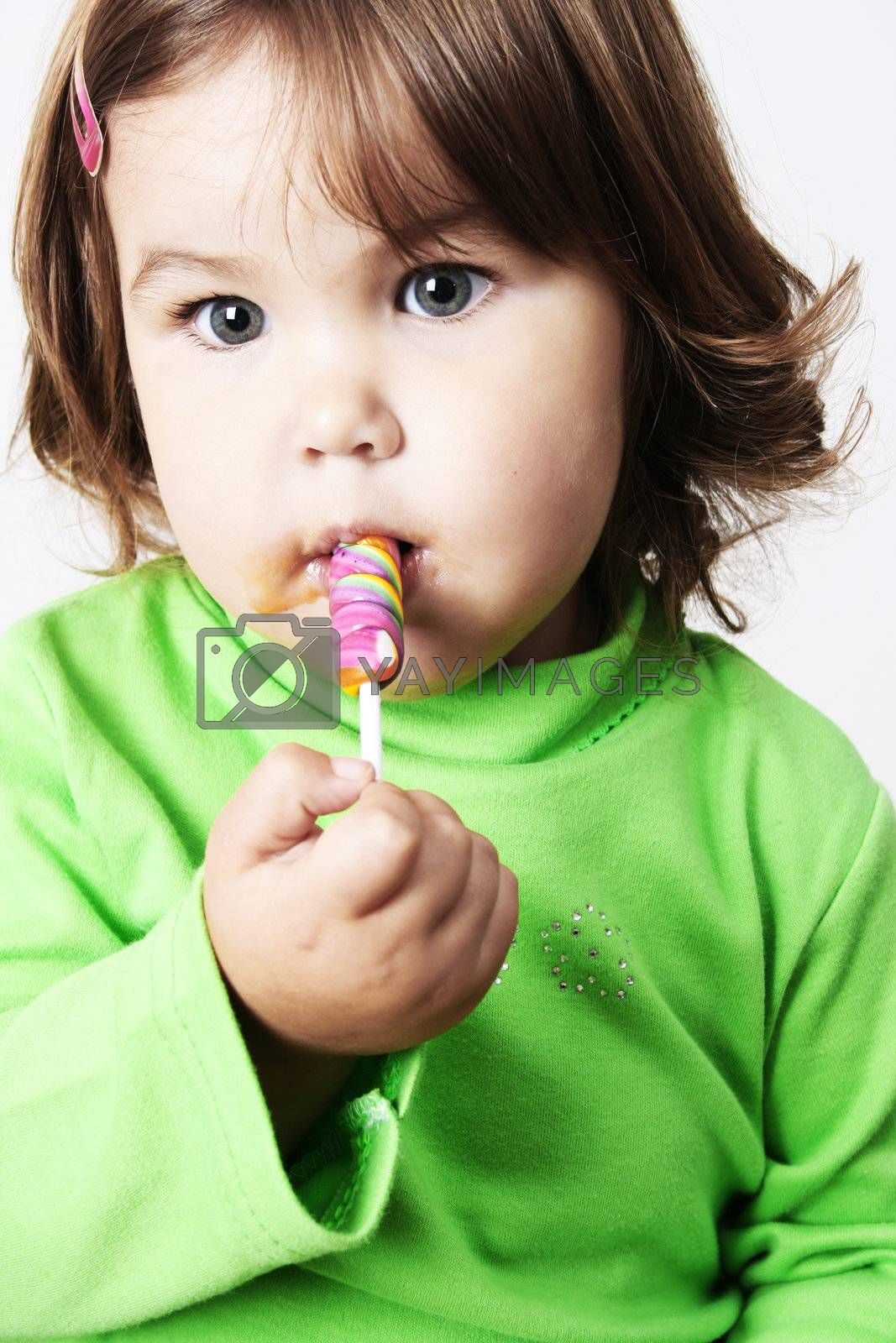 Toddler girl with chubby cheeks eating a sticky lollipop