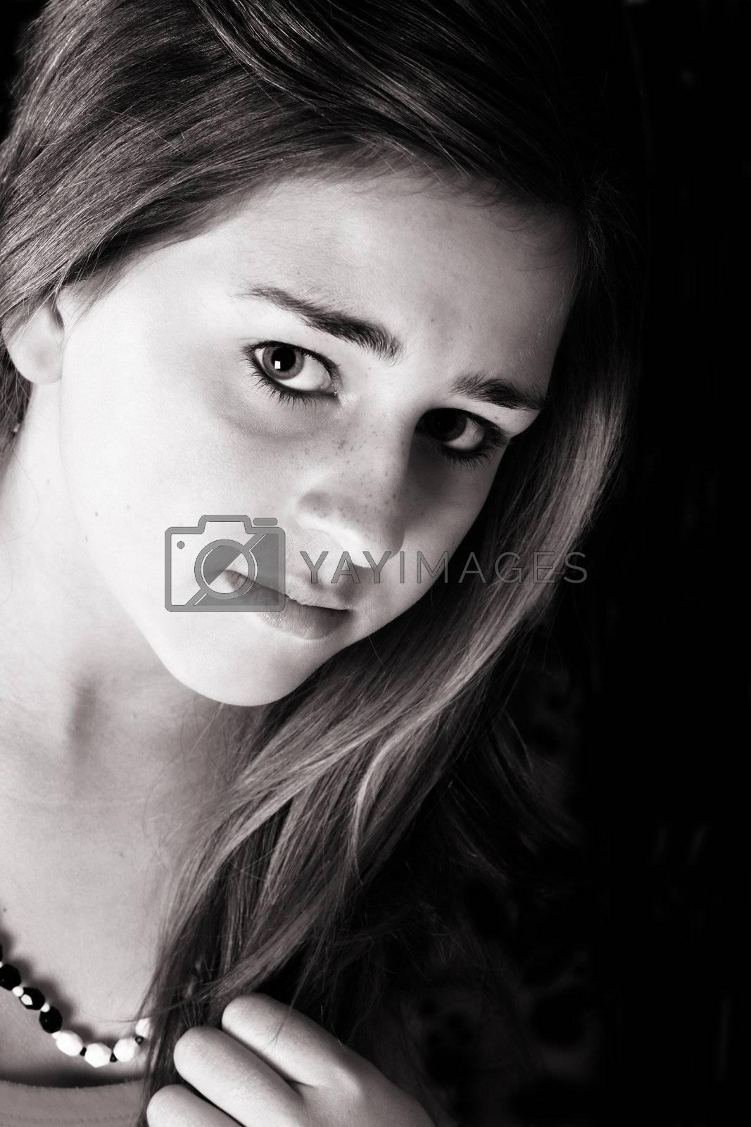 Beautiful teenage female against a black background
