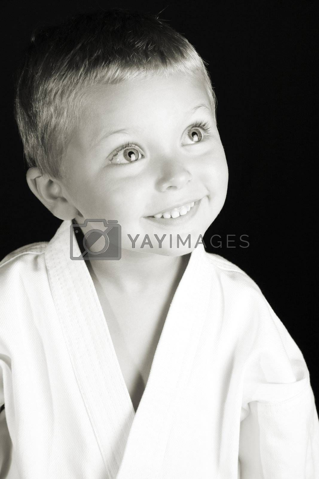 Young boy wearing his karate uniform on a black background