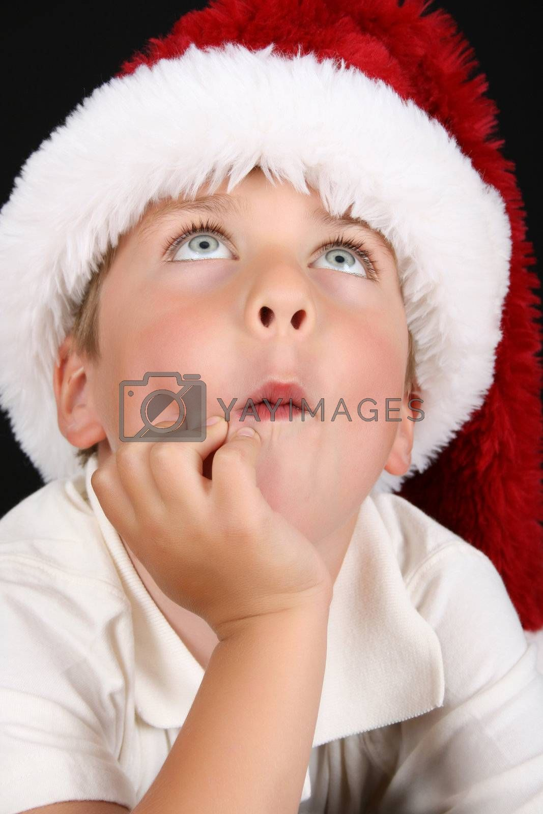 Cute christmas boy with beautiful blue eyes looking up