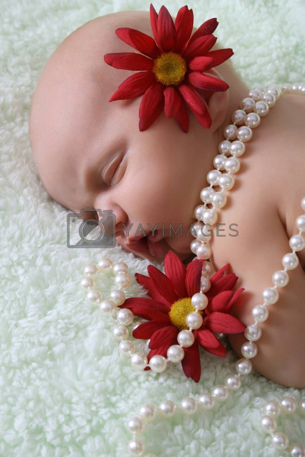 Beautiful newborn baby girl with flowers and pearls
