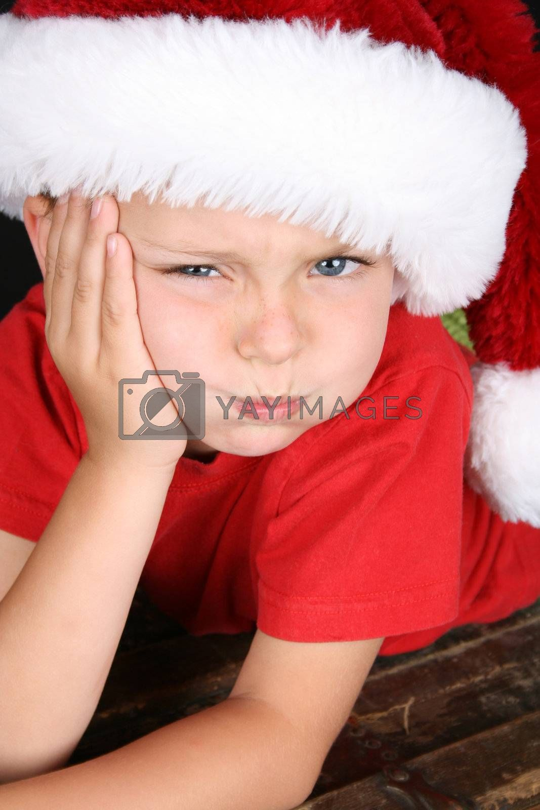 Bored little boy wearing a fluffy Christmas hat